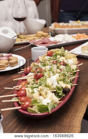 Main appetizer skewered tomatoes mozzarella cheese quiche coldcuts brownies and dips on the table
