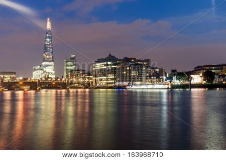 London, England - June 17 2016: Night Panorama of Southwark Bridge, The Shard  skyscraper and Thames River, London, United Kingdom