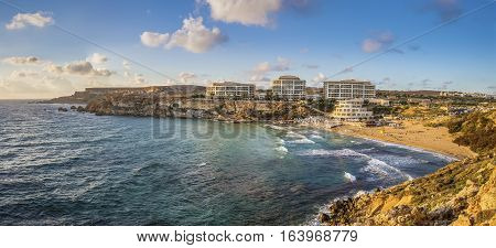 Ghajn Tuffieha Malta - Panoramic skyline view of Golden Bay Malta's most beautiful sandy beach at sunset with blue sky and clouds