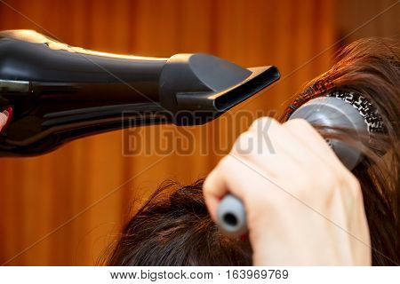 Girl dries hair and makes your hair with a comb