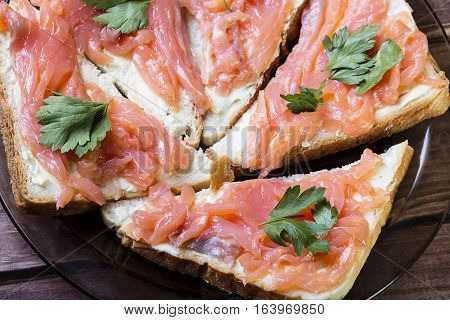 Sandwich wit salmon butter and herb on a wooden board.