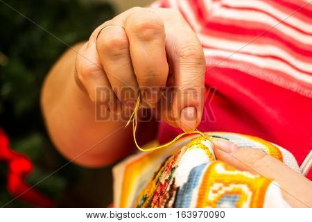 The cross stitching. Photo of woman hands closeup, which holds the needle and the embroidering.