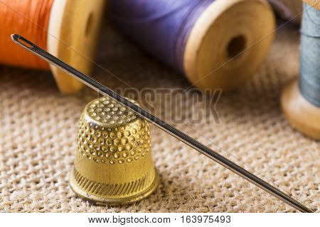 Sewing concept. Needle with thimble close up near thread spools on canvas background.
