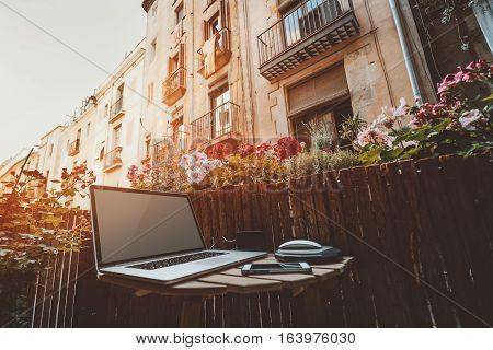 Small cozy beautiful workspace on balcony with laptop on wooden table mouse smartphone and a lot of flowers around on sunny summer day facades behind of historical district of Barcelona - El Born