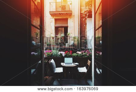 Small cozy beautiful workspace on balcony with laptop mouse smartphone two chairs and flowers around on sunny summer day seeing through opened doors from dark interior facade of house behind