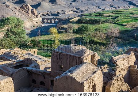 Abandoned mud brick village of Kharanaq in Iran with old aqueduct on background