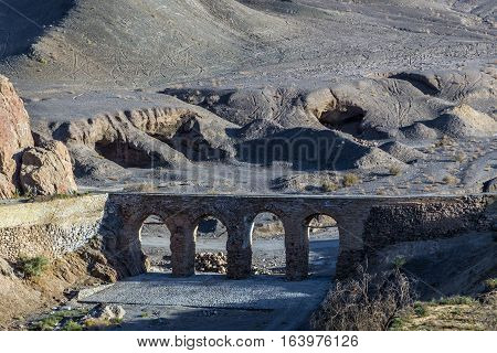 Old aqueduct seen from abandoned mud brick village of Kharanaq in Iran