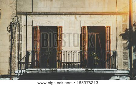 Close-up view of facade with balcony and two windows with opened blind and plants inside old house in touristic and historical district of Barcelona -El Born sunny summer day Spain