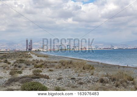Lady's Mile beach in Limassol Cyprus with the port in the background.  Wilderness meets industry.