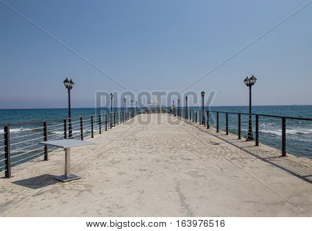 Long pier with arbour at the end.  This pier is at Amathous near Limassol in Cyprus and often used for a wedding venue.  In this shot there is just a fisherman.