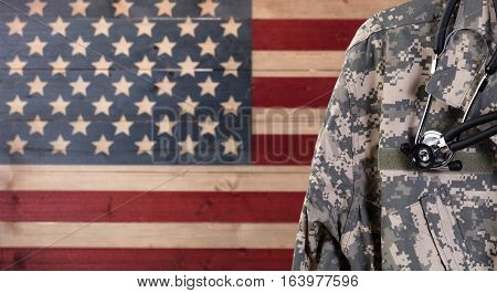 Closeup of military uniform with stethoscope against faded boards painted in USA flag background. Healthcare concept for American soldiers.