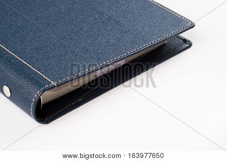 the corner Dark blue colored organizer book on white background