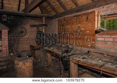 Interior of old ancient wooden forge with tools and instruments
