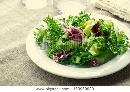 Green salad with spinach, frisee, arugula and radicchio on blue wooden background, toned, horizontal