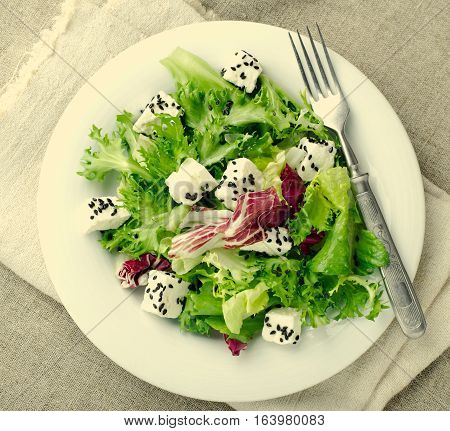 Green salad with spinach, frisee, arugula, radicchio, feta cheese and black sesame seed on blue wooden background, square, toned, top view