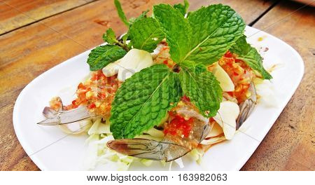 Spicy salad shrimp in fish sauce on wooden background Thai Seafood.
