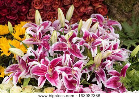 A beautiful flower arrangement outdoors, including roses and lilies.