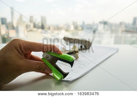 woman use green staple puller to remove staple from business document by left hand