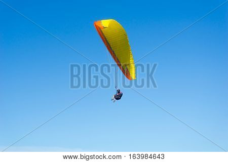 Mount Maunganui, New Zealand - December 21, 2016; Male para-glider enjoys the freedom flying in clear blue sky above the beach Mount Maunganui.