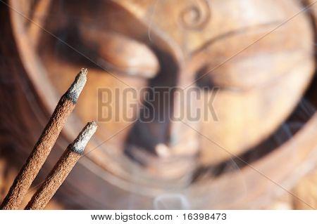 Smoldered sandal-wood incense and Buddha image background
