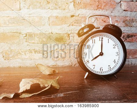 Retro black alarm clock with eight o'clock and dry leaves on wooden table and brick wall background