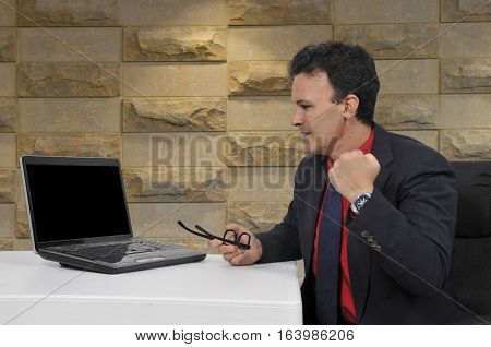 Handsome business man banker or salesman with a computerdoing a fist pump