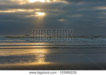 Shaft of sunlight poking through thick cloud cover over a Pacific beach in Washington's northwest