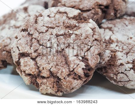 Chocolate with almond cookies in powdered sugar on white background