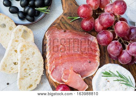 Cured meat, fresh baguette, grapes, cheese and black olives. Italian antipasti set. Close up view