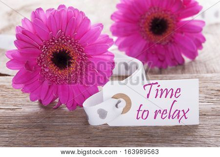 Label With English Text Time To Relax. Pink Spring Gerbera Blossom. Vintage, Rutic Or Aged Wooden Background. Card For Spring Greetings.