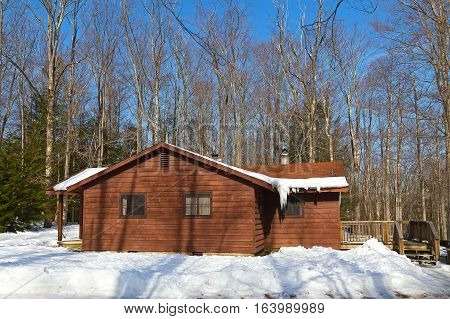 Cabin in the park covered in snow. A cozy cabin in the winter forest under blue sky.