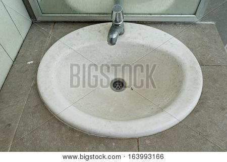 Dirty wash basin in men's public toilet