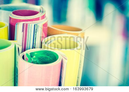 Close up edge of colorful magazine stacking roll with blurry bookshelf background for publication and publishing concept extremely DOF with vintage retro color tone