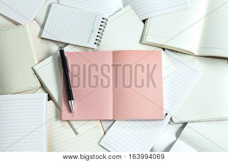 Manny empty notebook paper and note pad background with one pink book
