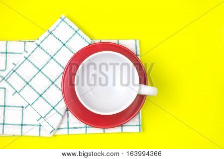 the top view of empty white coffee or tea cup with red dish and towel on vibrant color background