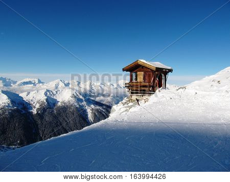A Mountain Hut On The Side Of A Snow Covered Alpine Piste