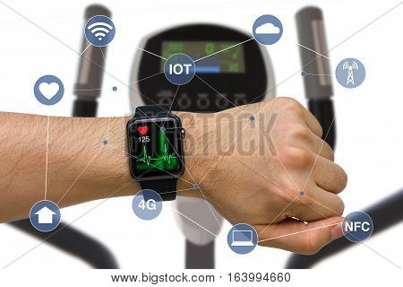 Concept of smart watch monitoring heart rate application while exercising with elliptical machine.