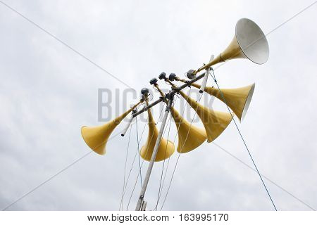 six large yellow loudspeakers mounted on a pole in the air