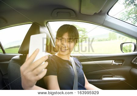 Woman taking a photo with smart phone in car with sunlight,Woman selfie in car