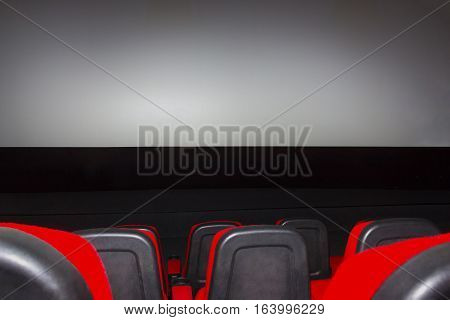 The empty movie theater with red seats and screen