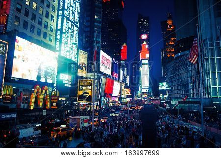 New York, United States - September 13, 2014. Times Square at night, with commercial buildigs, street traffic and people.