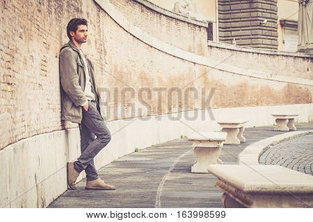 Young male fashion street on wall. A beautiful young man wearing winter clothes in the street. Pants, white sweater and green long coat. Hands in his pockets, leaning on an old wall. Intense attractive look, stylish hair.