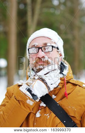 Portrait of a bearded man frozen in a Blizzard in the woods. Face and glasses covered with snow. He takes the snowflakes from his beard.