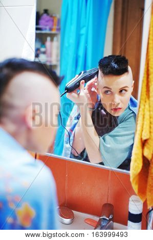 Young pretty woman looks in the mirror and doing her hair shave hair at the temples clipper in bathroom