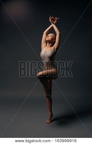Female sexy gymnast in beige bodysuit posing on gray background streching gracefully with hands over her head and looking up