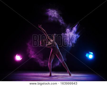Female sexy gymnast in beige bodysuit bending gracefully with her hands up on gray background with colored dust all over body shot made with color filter.