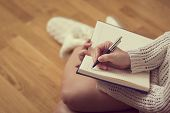 Detail of a young woman holding a planner and writing in her diary enjoying winter days in a cozy home atmosphere poster