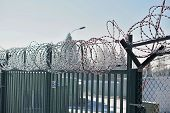 High metal fence with a sharp barbed wire on the top covered by snow in winter as a symbol of restricted access and protection of the area poster