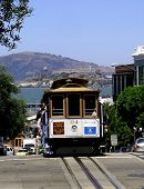 Photograph of a San Francisco Cable Car descending to the wharf area. Also seen in the background is Alcatraz Island. poster
