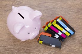 Set Of Printer Ink Cartridges With A Piggy Bank